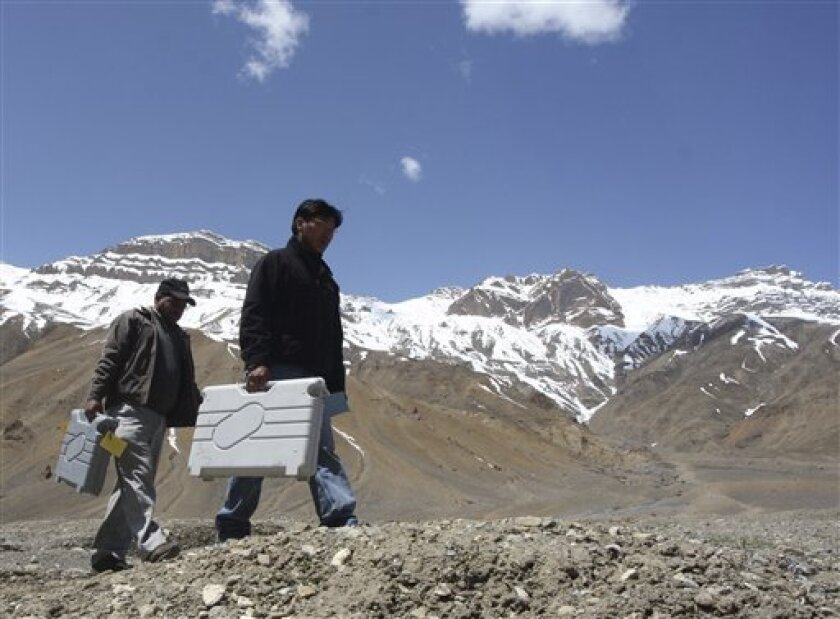 Polling officials hold electronic voting machines and walk towards their allotted polling booths at Kaza, in the northern Indian state of Himachal Pradesh, Tuesday, May 12, 2009. The last phase of the five-phased general elections will be held on May 13. (AP Photo/Anil Dayal)