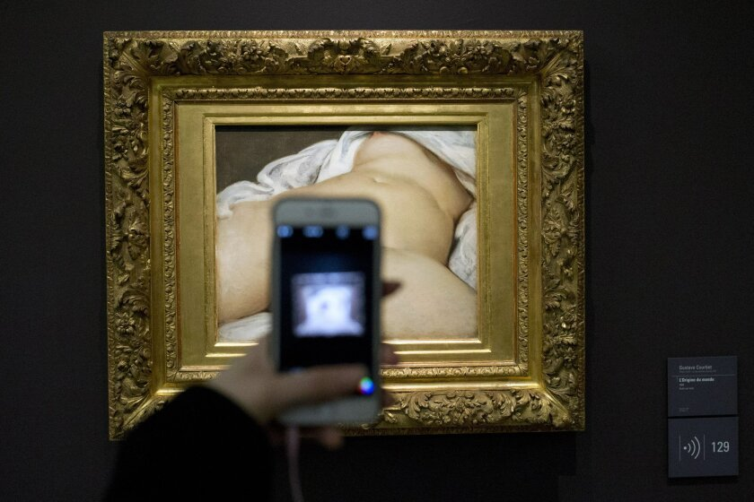 """A visitor takes a picture with a phone of Gustave Courbet's 1866 """"The Origin of the World,"""" painting which depicts female genitalia at Musee d'Orsay museum, in Paris, France, Friday, Feb. 12, 2016.  Facebook lost a crucial legal battle Friday as a Paris court ruled the social network can be sued in"""
