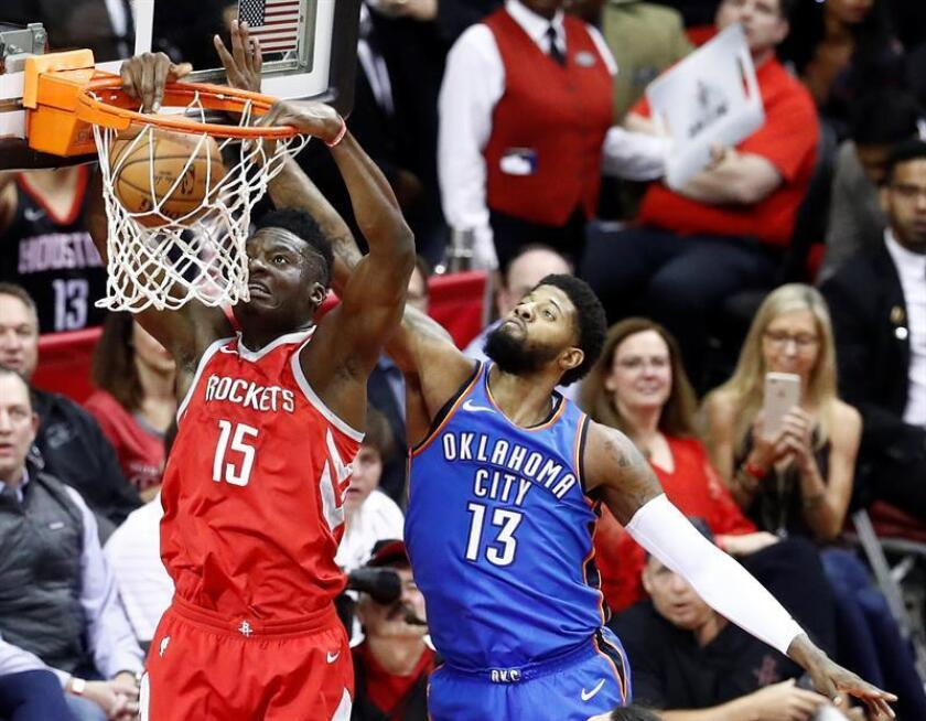 Oklahoma City Thunder player Paul George (R) tries to block a dunk against Houston Rockets player Clint Capela (L) in the first half of their NBA basketball game at the Toyota Center in Houston, Texas, USA, 07 April 2018. EFE