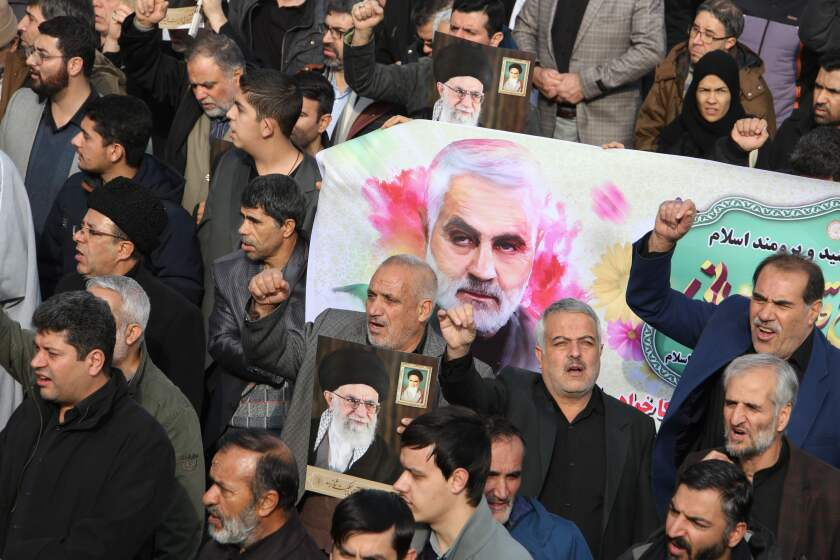 Iranians march with a banner bearing an illustration of Quds Force leader Qassem Suleimani during a demonstration in Tehran on Friday.
