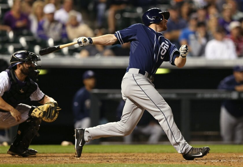 San Diego Padres pinch-hitter Cory Spangenberg watches his two-run home run in front of Colorado Rockies catcher Michael McKenry during the seventh inning of the Rockies' 7-6 victory in 12 innings in a baseball game in Denver on Saturday, Sept. 6, 2014. (AP Photo/David Zalubowski)