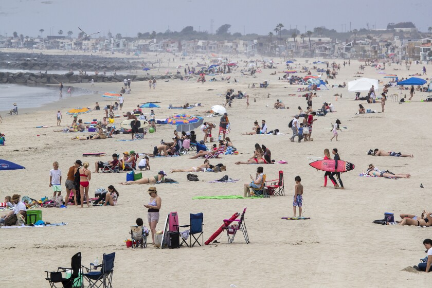 NEWPORT BEACH, CA -- TUESDAY, APRIL 28, 2020: Beach-goers enjoy a partially-sunny, warm day on the beach near the pier in Newport Beach, CA, on April 28, 2020. Newport Beach City Council members are holding a special meeting to discuss closing the city's beaches for the next few weekends following Gov. Gavin Newsom's criticism of the large crowds and lack of social distancing.(Allen J. Schaben / Los Angeles Times)