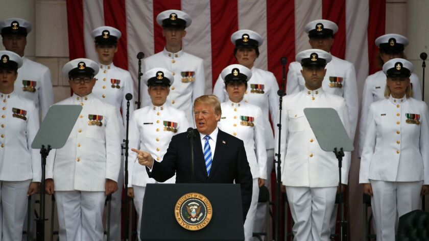 President Donald Trump pauses at the podium as he arrives for a ceremony at the Memorial Amphitheate