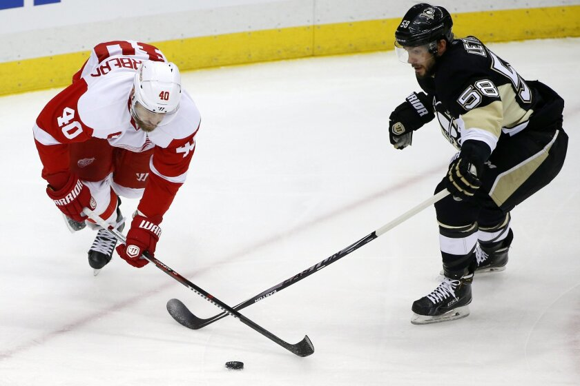 Detroit Red Wings' Henrik Zetterberg (40) loses control of the puck as he falls, with Pittsburgh Penguins' Kris Letang (58) defending during the first period of an NHL hockey game in Pittsburgh, Thursday, Feb. 18, 2016. (AP Photo/Gene J. Puskar)