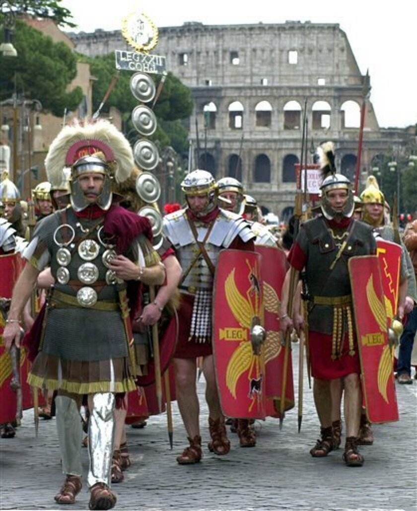 """FILE - In this Sunday, April 18, 2003 file photo, people dressed as Roman centurions march in front of Rome's Colosseum. Rome's policemen donned togas, capes and sandals in an undercover operation that broke an alleged ring of """"gladiators"""" outside the Colosseum and other landmarks in the Italian ca"""