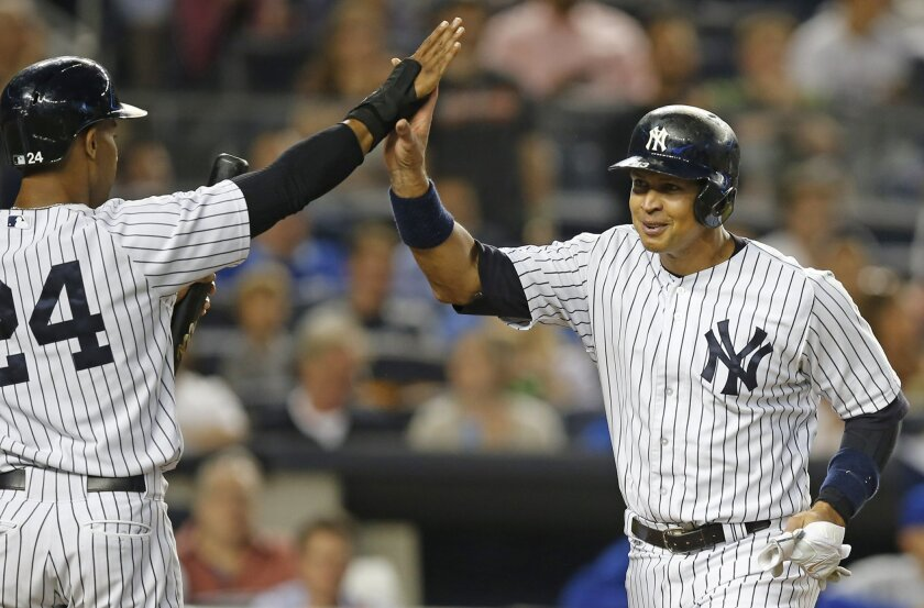 New York Yankees Chris Young (24) greets Alex Rodriguez after they scored on Mark Teixeira's fifth-inning double in a baseball game against the Kansas City Royals at Yankee Stadium in New York, Tuesday, May 26, 2015. (AP Photo/Kathy Willens)