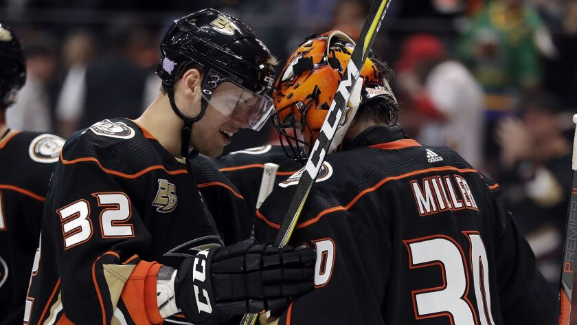Ducks goaltender Ryan Miller (30) and defenseman Jacob Larsson (32) celebrate the team's 3-2 win over the Calgary Flames.