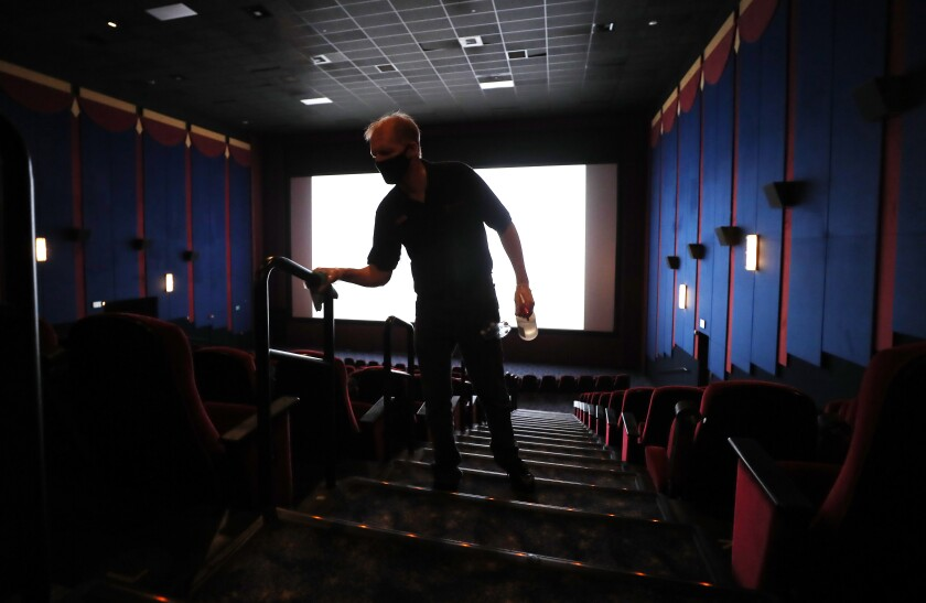 A worker cleans a La Mesa movie theater on the first day of being open since the COVID-19 pandemic shutdown.