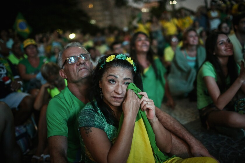 A pro-impeachment supporter wipes a tear with her Brazilian flag while watching a live television broadcast as lower house deputies voted to impeach President Dilma Rousseff on April 17, 2016.
