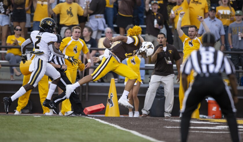 Wyoming quarterback Sean Chambers leaps for a touchdown in the Cowboys' season-opening win against Missouri.