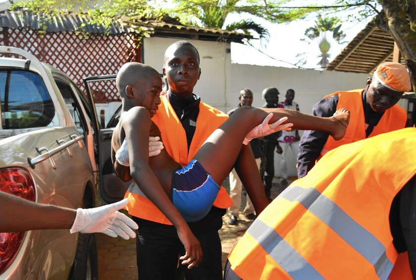 An emergency worker carries a boy injured in one of the attacks on hotels in Grand Bassam, Ivory Coast, on March 13.