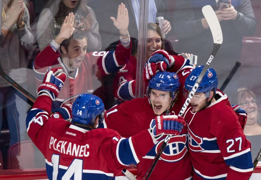 Montreal Canadiens' Brendan Gallagher celebrates his goal against the Tampa Bay Lightning with teammates Tomas Plekanec, left, and Alex Galchenyuk, right, during the first period of an NHL hockey game, Tuesday, Feb. 9, 2016, in Montreal.  (Paul Chiasson/The Canadian Press via AP) MANDATORY CREDIT