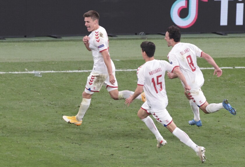 Denmark's Joakim Maehle, left, celebrates after scoring his side's fourth goal during the Euro 2020 soccer championship group B match between Russia and Denmark at the Parken stadium in Copenhagen, Denmark, Monday, June 21, 2021. (AP Photo/Hannah McKay, Pool)
