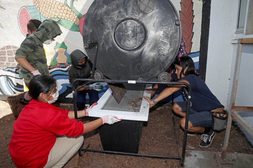 Science teacher Monique Sweet, right, shows sixth-graders how to use a compost bin at Costa Mesa's Rea Elementary School.