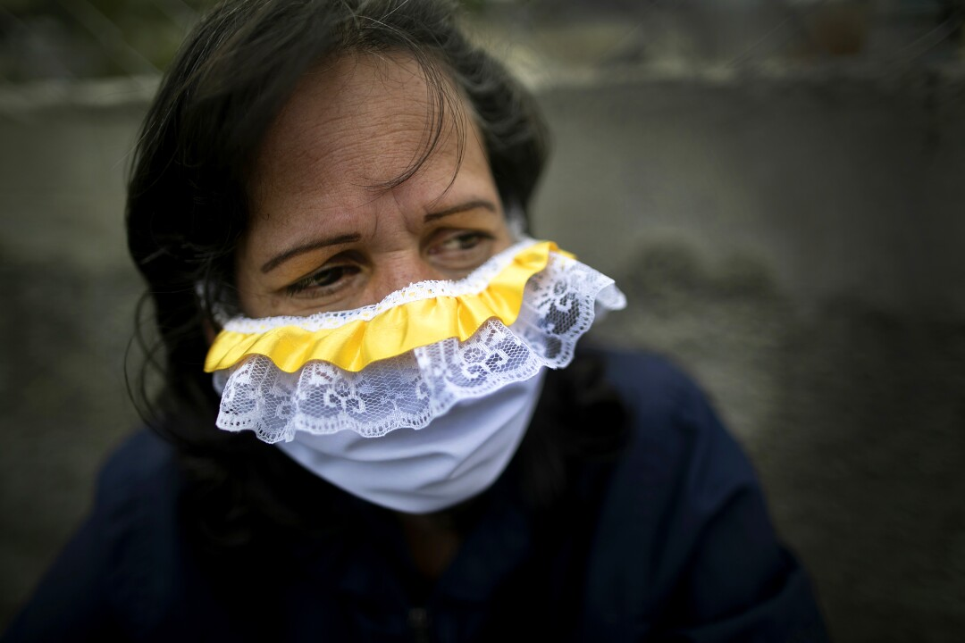 VENEZUELA: A woman wears a lacey homemade face mask as a precaution against the coronavirus as she waits in line to buy food in Caracas.
