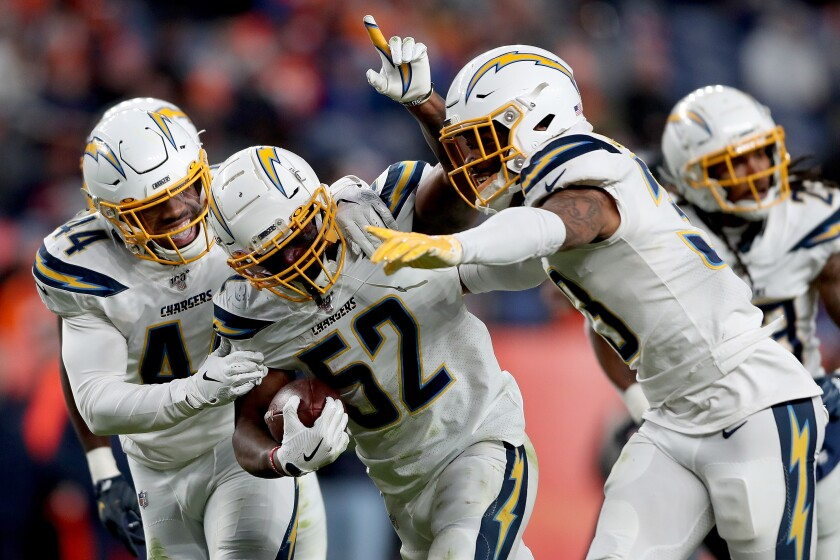 Denzel Perryman (52) celebrates with his fellow linebackers Kyzir White (44) and Derwin James (33) after intercepting a pass during their game against the Broncos on Dec. 1.