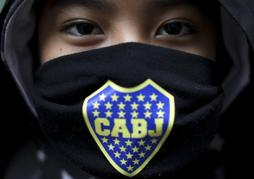 Thiago Laura posa para una foto con una mascarilla de Boca Juniors mientras espera por comida en un comedor comunitario