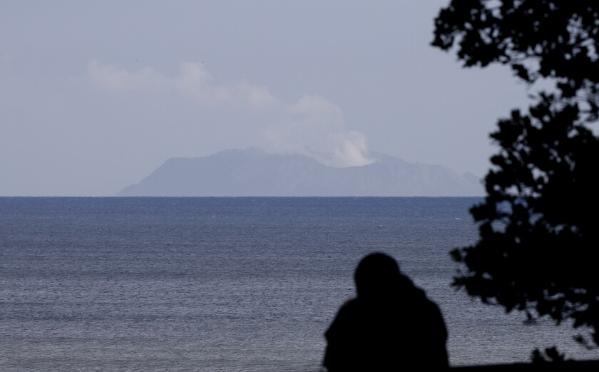 A man watches as a plume of steam is seen above White Island early morning off the coast of Whakatane, New Zealand, Tuesday, Dec. 10, 2019. A volcanic island in New Zealand erupted Monday Dec. 9 in a tower of ash and steam while dozens of tourists were exploring the moon-like surface, killing at least five people and leaving many more missing.(AP Photo/Mark Baker)