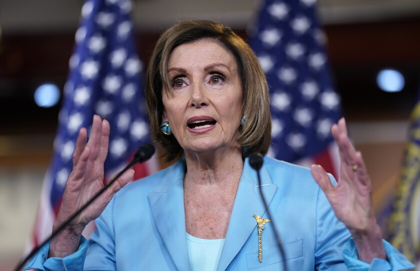 Speaker of the House Nancy Pelosi talks at a microphone with her hands up on either side of her.