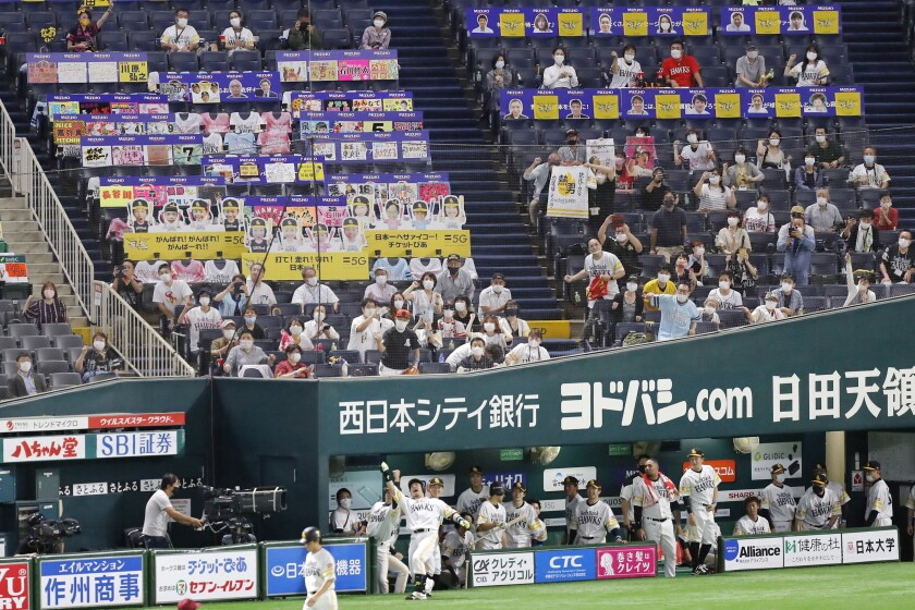 FILE - In this July 10, 2020, file photo, fans wearing face masks cheer as SoftBank Hawks' Nobuhiro Matsuda, center, celebrates after hitting a solo home run against Rakuten Golden Eagles in the second inning of a regular season baseball game in Fukuoka, southwestern Japan. Japan's baseball and soccer leagues are ready to allow more fans into their games. The head of Japanese baseball and the soccer J-League on Tuesday, Sept. 8, 2020, said they are asking the government to allow a maximum of 20,000 fans, or up of 50% capacity — whichever number is smaller. (Kyodo News via AP, File)