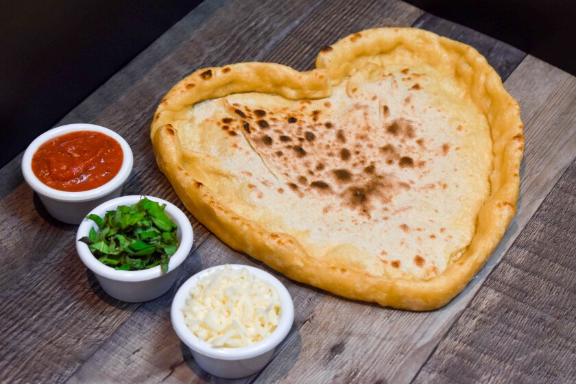 Sammy's Woodfired Pizza is warming our hearts with this heart-shaped pizza kit, with a par-baked, heart-shaped crust, tomato sauce, mozzarella and basil.