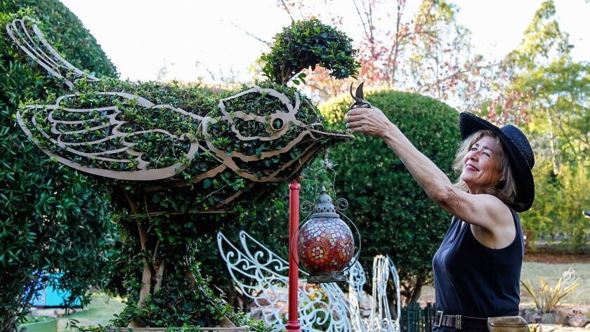 Jennifer Coburn trims greenery on a bird topiary at her Elfin Forest property.