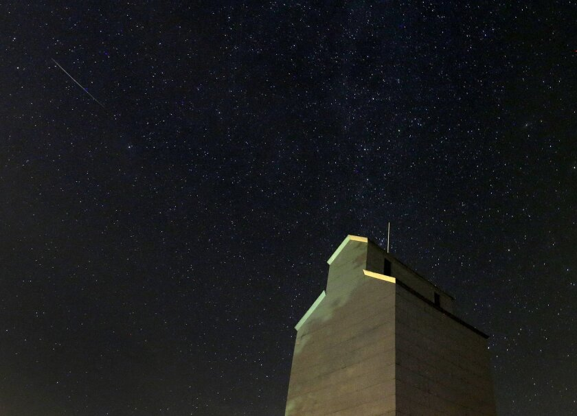 A meteor streaks across the sky behind a grain elevator during the annual Perseid meteor shower Thursday,  in Baxter, Iowa.
