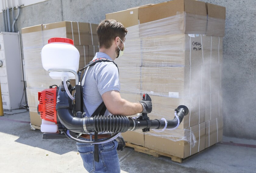 Using a sprayer called the Tomahawk Fogger, Jim Nora, national account sales manager at Tomahawk, sanitizes two pallets of merchandise at the company's warehouse in the Otay Mesa on Friday.