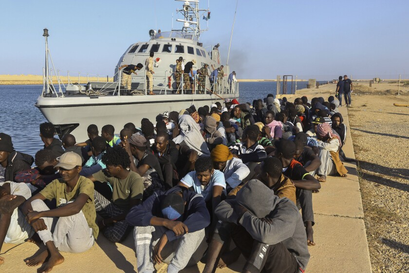 FILE - In this Tuesday, Oct. 1, 2019 file photo, rescued migrants are seated next to a coast guard boat in the city of Khoms, Libya, around 120 kilometers (75 miles) east of Tripoli. Investigators commissioned by the United Nations' top human rights body to examine possible abuses said Monday they have turned up evidence of possible war crimes and crimes against humanity in Libya, in particular against migrants looking to use the restive North African country as way to get to Europe. (AP Photo/Hazem Ahmed,File)