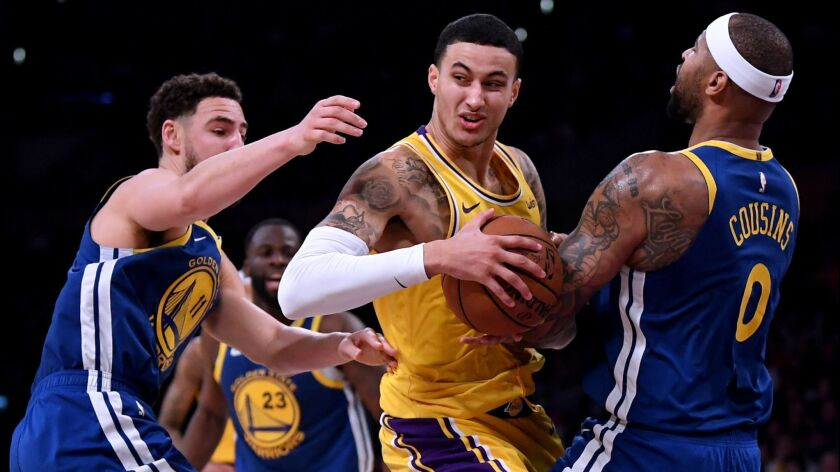 Kyle Kuzma is fouled by Golden State's DeMarcus Cousins as he drives past Klay Thompson during a game on Jan. 21 at Staples Center.