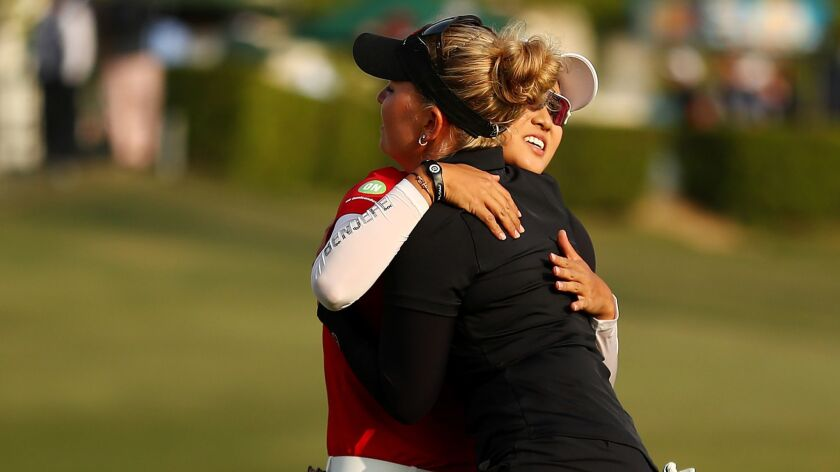 Minjee Lee and Nanna Koerstz Madsen hug after the completion of the third round at Wilshire Country Club.