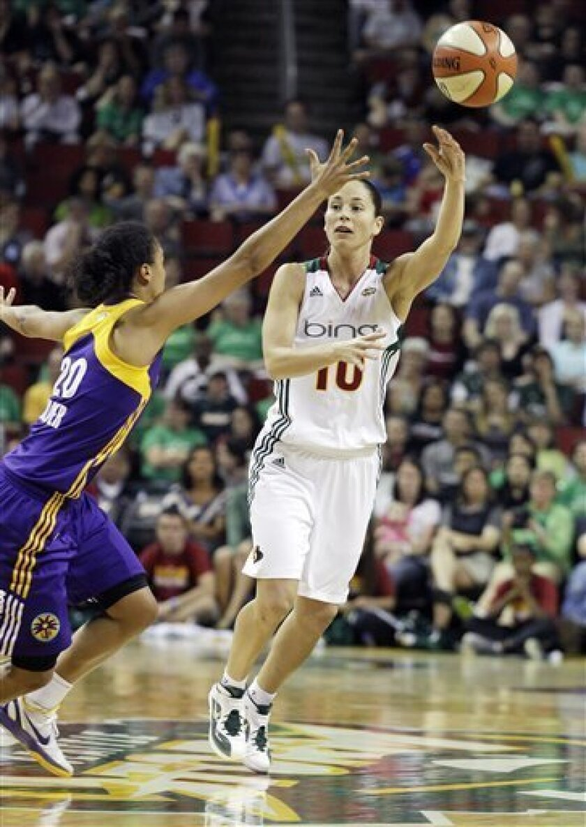 Seattle Storm's Sue Bird (10) passes around Los Angeles Sparks' Kristi Toliver, left, in the first half of a WNBA basketball game, Saturday, July 9, 2011, in Seattle. (AP Photo/Ted S. Warren)