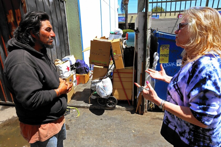 Florist shop owner Bonnie Bernard, right, talks with Angel, a homeless man who has been living with his wife across the way from Bernard's store in a Sylmar shopping center.