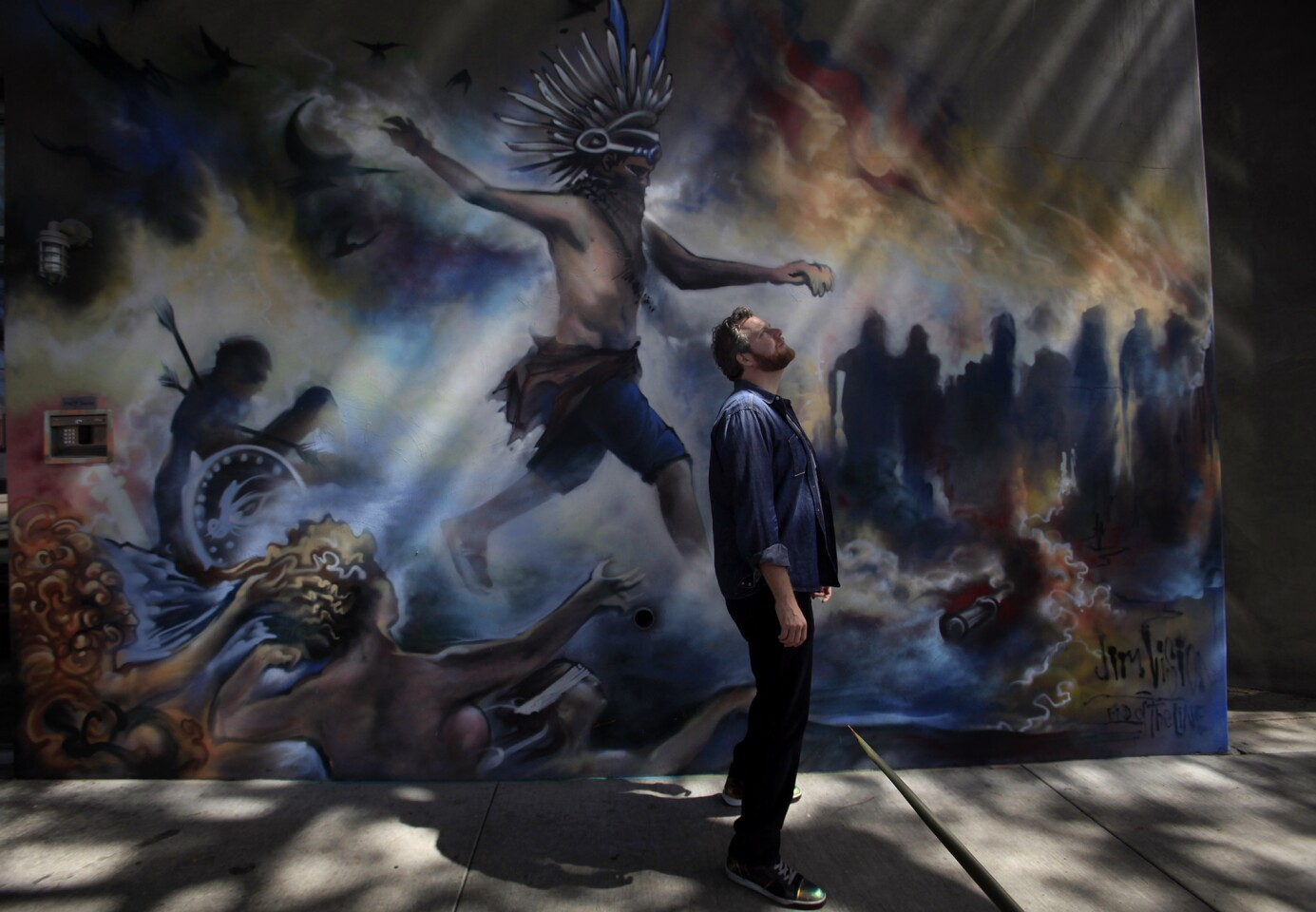 Oliver Luckett, cofounder and chief executive of tech start-up theAudience, stands in front of a mural painted by street artist Jim Rockwell, a.k.a. Jim Vision, on one of his offices in Los Angeles.