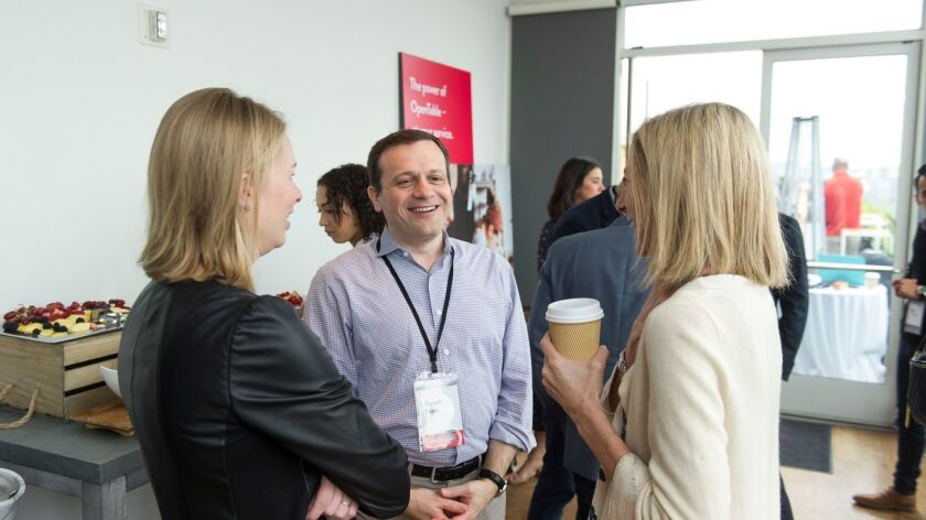 OpenTable Chief Technology Officer Joseph Essas, center, has a conversation during the company's inn