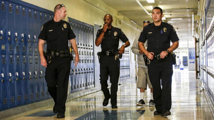 El oficial de policía Henry Anderson (segundo, de izquierda a derecha) acompañado por oficiales de Gardena en la Robert E. Peary Middle School, de esa ciudad (Irfan Khan / Los Angeles Times).