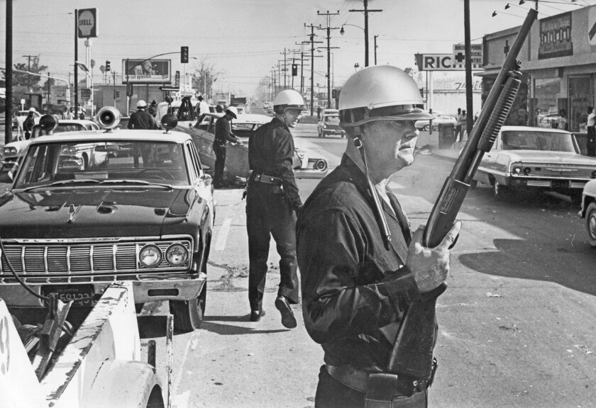 Los Angeles police officers stand guard as debris from a day of violence is cleared from the intersection of Avalon Boulevard and Imperial Highway. Staff file photo from 1965 Watts riots.