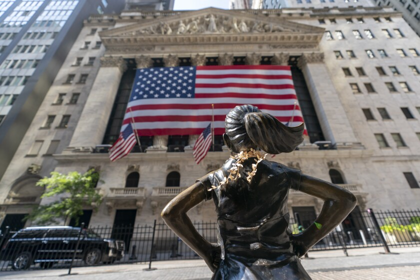 """The """"Fearless Girl"""" sculpture looks toward the New York Stock Exchange."""