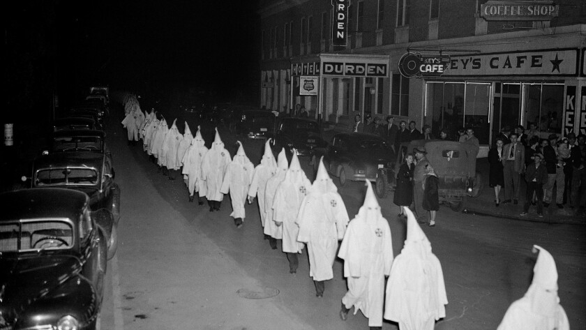 In this Feb. 3, 1948, photo, members of the Ku Klux Klan wear white hoods and robes as they march around the town square in Swainsboro, Ga.