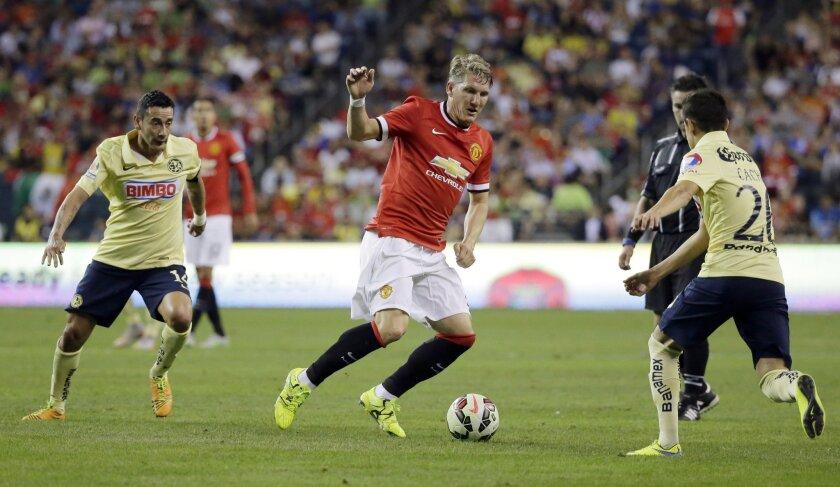 Bastian Schweinsteiger (c) del United escapa a la marca de Francisco Rivera (d) y Rubens Sambueza (i).