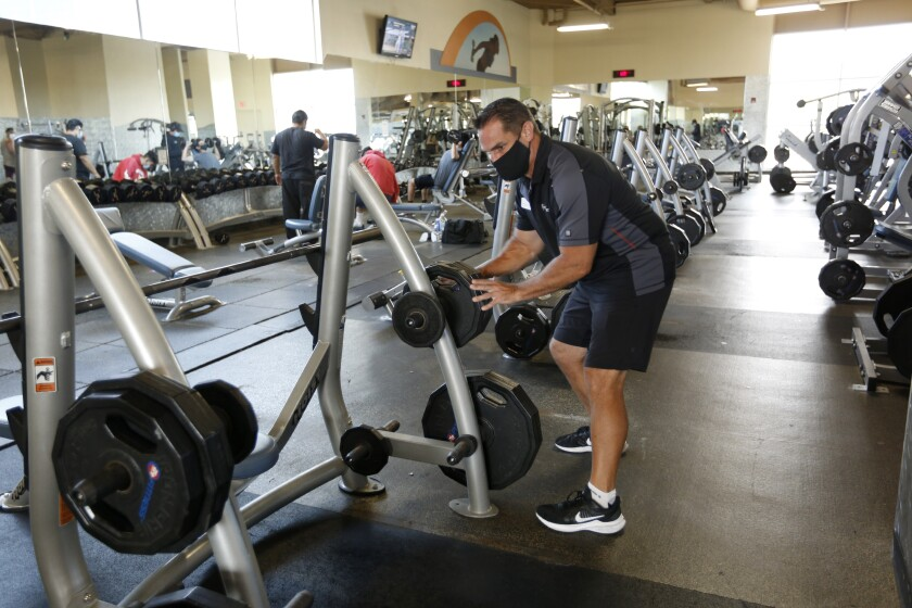 Andrew Dewey makes sure weights are properly stored on the first day 24-Hour Fitness reopened