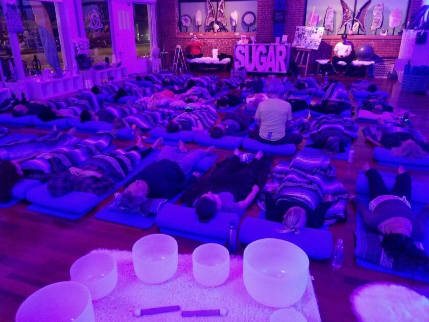 Patrons participating in a sound bath session in the Love room at Be Crystal Clear.