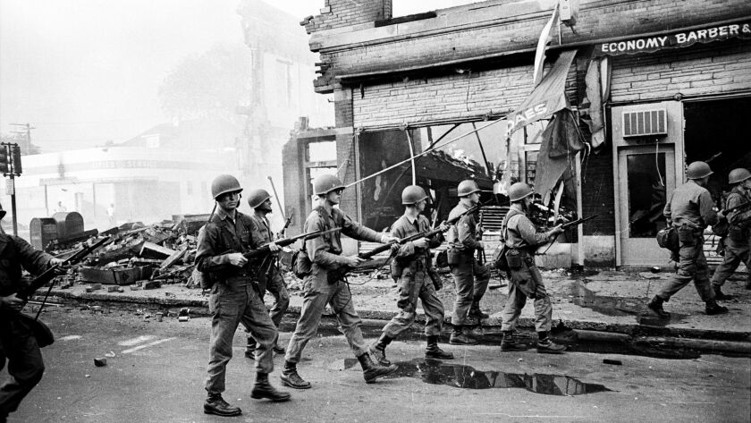 The National Guard does a sweep on 12th Street, with bayonets attached to their rifles.