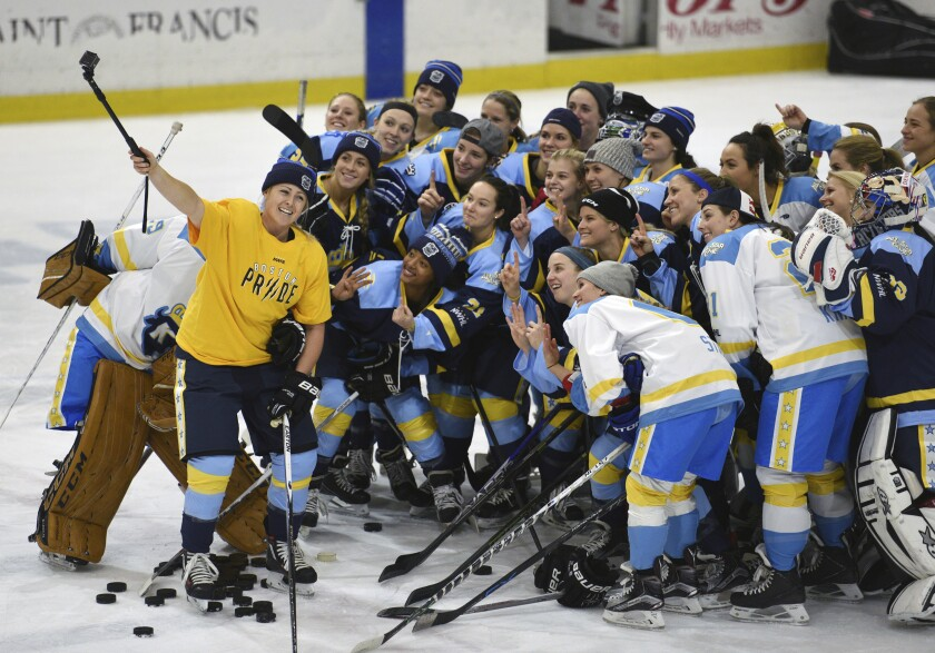 """FILE - In this Jan. 24, 2016, file photo, National Women's Hockey League All-Star players take time for a """"selfie"""" before the start of an all-star game at Harborcenter in Buffalo, N.Y. The National Women's Hockey League will complete its abbreviated season with two nationally televised semifinals and a championship game. The move comes two months after the league suspended its playoffs following a COVID-19 breakout among numerous teams. Play will resume outside of Boston with the semifinals on March 26, followed by the Isobel Cup Final the next day. (AP Photo/Gary Wiepert, File)"""