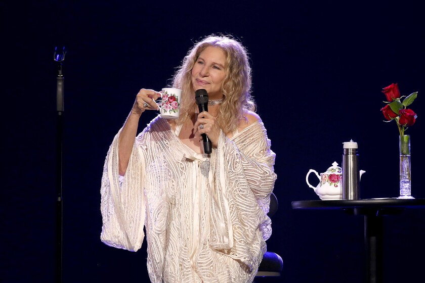 Barbra Streisand, in a white gown, holds a microphone and cup of tea