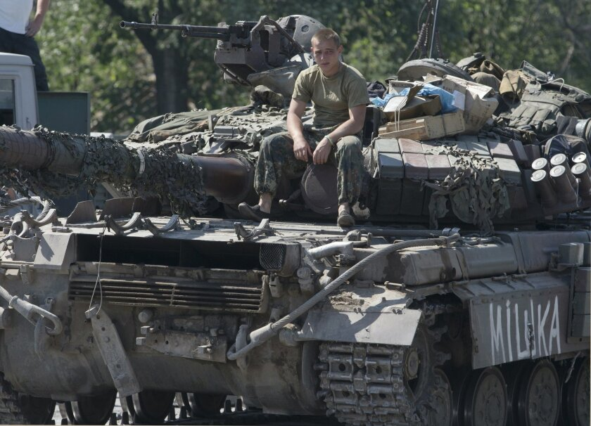 A Ukrainian government army soldier rests on his tank at a block-post in the village of Debaltseve, eastern Ukraine Friday, Aug. 1, 2014. With the sound of artillery blasts at a distance, dozens of international investigators arrived Friday at the eastern Ukraine site where Malaysia Airlines Flight 17 crashed and began a painstaking search for the remains of as many as 80 victims. (AP Photo/Dmitry Lovetsky)