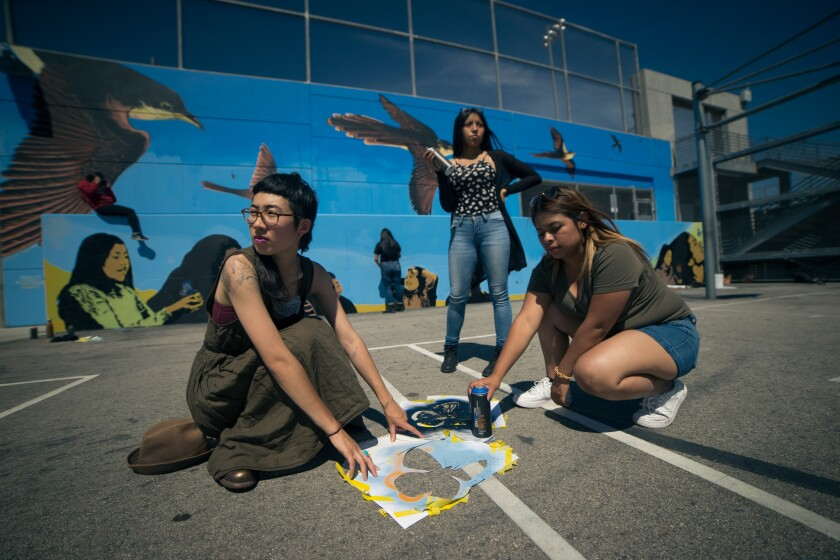Artist and high school students working on mural of yellow-billed cuckoos