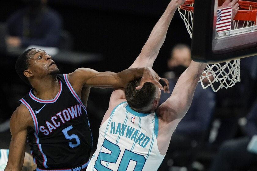 Charlotte Hornets forward Gordon Hayward is fouled by Sacramento Kings guard De'Aaron Fox during the second half of an NBA basketball game on Monday, March 15, 2021, in Charlotte, N.C. (AP Photo/Chris Carlson)