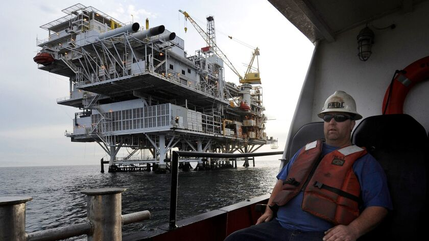 FILE - In this May 1, 2009 file photo, a crew member arrives by boat at th offshore oil drilling pla
