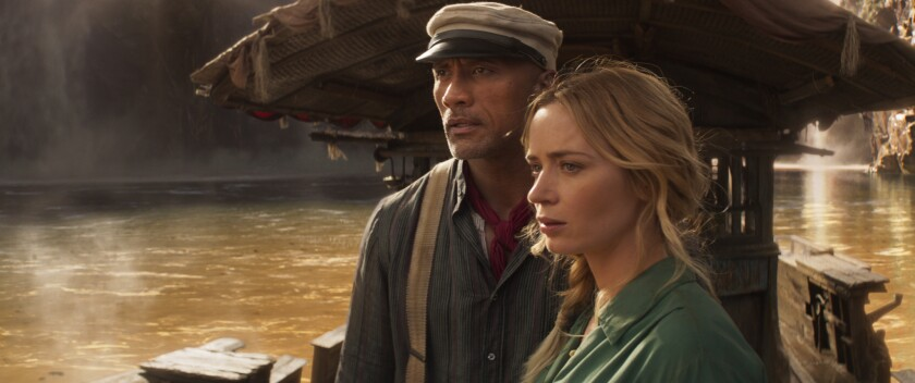 A man in suspenders and a cap, left, and a woman stand on a boat on a muddy river
